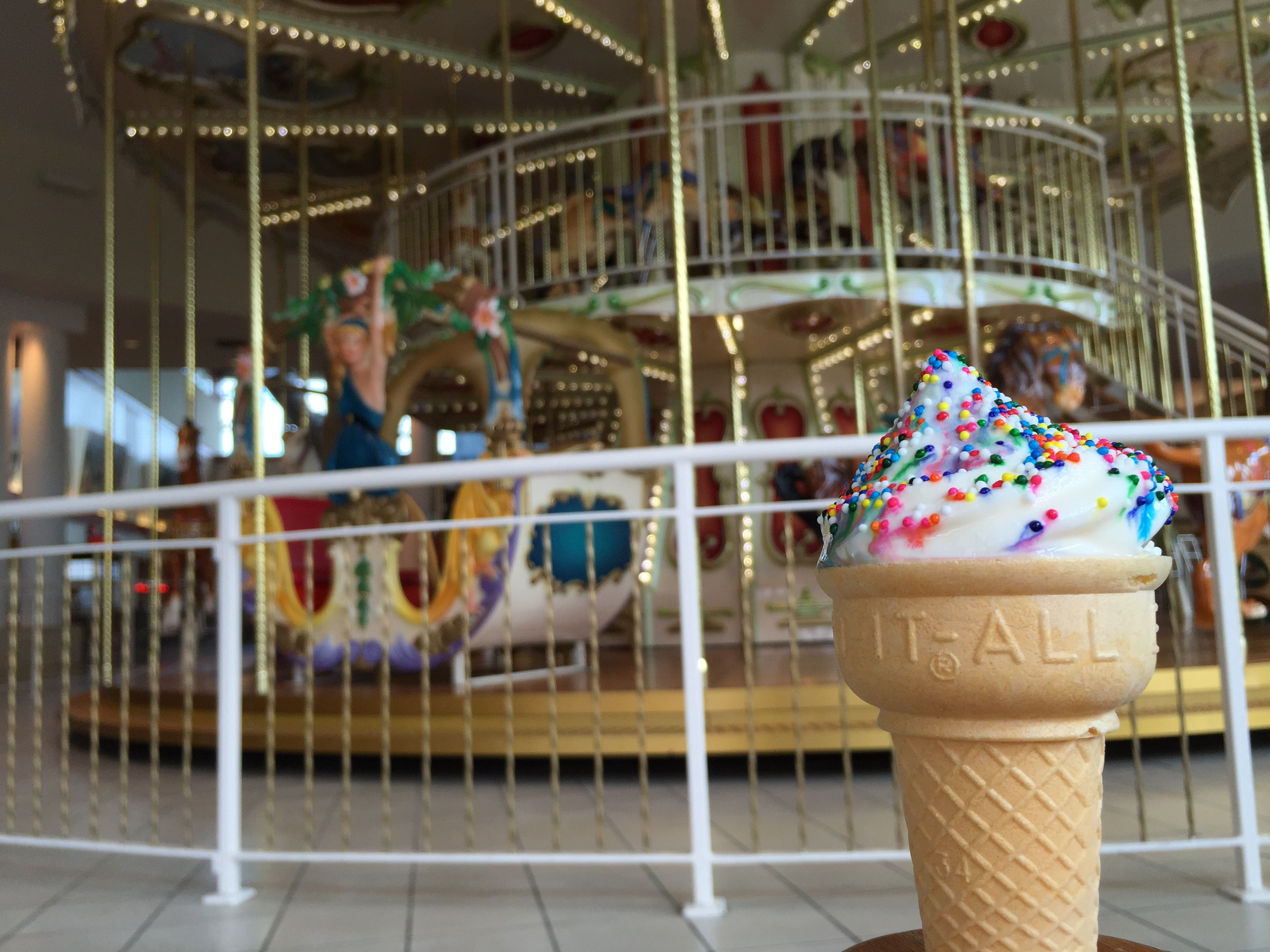 ice cream cone with sprinkles in front of a carousel